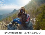 Small photo of Adventurous female photographer sitting on the rock while photographing mountains facing the camera against setting sun. Wide angle perspective. Tourism, adventure, hiking concept.