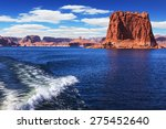 Foamy trace of a motor boat crosses the emerald waters. In the distance the coast of red sandstone. Lake Powell on the Colorado River - stock photo
