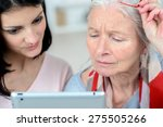 helping old woman use a tablet... | Shutterstock . vector #275505266