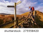 a woman crossing a stile on the ...