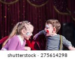 Small photo of Cute funny boy and girl with painted faces acting as a couple with communication problems, during a theatrical performance