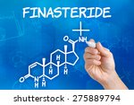 Small photo of Hand with pen drawing the chemical formula of Finasteride