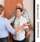 Small photo of Positive daughter greeting elderly parents at threshold