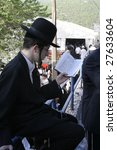 Small photo of MERON, ISRAEL - MAY 6: Young Lag Ba'omer pilgrim with hat and payot reading the Torah during the festivities May 6, 2007 in Meron.