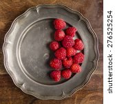 Small photo of Fresh raspberries arranged on an antique pewter plate. Photographed from above.