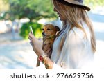 Stock photo portrait of beautiful young woman with her dog using mobile phone 276629756