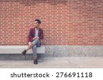 Young handsome Asian model dressed in red blazer sitting on a marble bench in the city streets