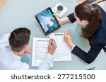 Small photo of Young business couple discussing rental agreement. Woman showing man office buildings on digital tablet at table.