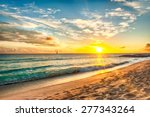 Stock photo beautiful sunset over the sea with a view at stony shore on the white beach on a caribbean island 277343264