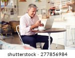 Small photo of Middle aged man sitting in a cafe