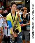 Small photo of Bangkok, Thailand - December 15, 2010: Musician playing his saxophone performs with a group at an impromptu concert on Khao San Road