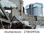 Small photo of Dirty abandoned trash ruins with modern office building at background. Concept of old and new contrast, rich and poor.