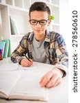 Small photo of Portrait of teenager in glasses sitting at the table and doing homework at home.