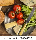 Small photo of Ploughmans lunch with cheese, bread rolls, tomatoes, lettuce on a vintage pewter plate. Shot from above.