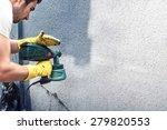Man painting a grey wall, renovating exterior walls of new house - stock photo