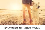 Stock photo hipster girl playing with dog at a beach during sunset strong lens flare effect 280679333