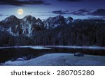 composite landscape with CGI elements. lake with boulder on the shore near the pine forest in mountains with 3D stone peaks at night in full moon light - stock photo
