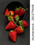 Small photo of red ripe strawberries on a black slate stone trivet