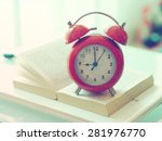 Red Alarm Clock On The Book...