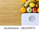 Healthy eating, fitness and weight loss concept, white scale with fruit on a wooden table with copy space