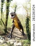 Small photo of April 10, 2015 Prehistoric Park, Rivolta D' adda, Lombardy, Italy :Scary Statue of a Large Allosaurus Dinosaur from Late Jurassic Period Standing at the Rocky Forest with Open Mouth