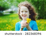 Small photo of Cute little girl with yellow dandelions in the field. Background toning to instagram filter.