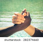 Small photo of Black and white human hands in peaceful handshake representing friendship and respect - Arm wrestling together against racism - Vintage filtered look