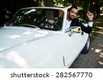 Successful and wealthy businessman sitting behind the wheel of his luxury cabriolet car on countryside road, sure and confident handsome man sits in his new convertible car outdoors looking so happy - stock photo