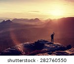 Stock photo man takes photos with smart phone on peak of rock empire dreamy fogy landscape spring orange pink 282760550