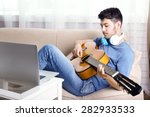 Young Man With Guitar On Sofa...