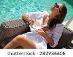 Woman Relaxing At The Poolside...