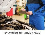 Taking a look under a hood. Close-up of man in uniform examining car and writing something in clipboard while standing in workshop - stock photo