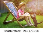 Stock photo boy sitting on a lounge chair and playing with a cat 283173218