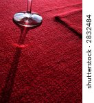 glass casting shadow on red table-cloth - stock photo
