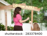 Two young girls painting a lemonade stand. One girl holds the container of yellow paint while the other girl paints the sign. - stock photo