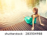 Young Woman Sitting On A Deck...