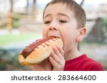 little boy eats a huge hot dog... | Shutterstock . vector #283664600
