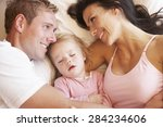 family relaxing in bed | Shutterstock . vector #284234606