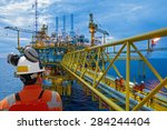 Worker And Oil Rig Background....