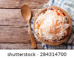 Small photo of sauerkraut and carrots in a wooden plate. horizontal view from above, rustic style