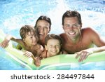Family On Holiday In Swimming...