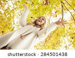 Woman Throwing Autumn Leaves...