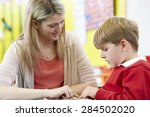 teacher helping male pupil with ... | Shutterstock . vector #284502020