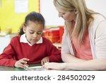 teacher helping female pupil... | Shutterstock . vector #284502029