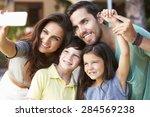 family in garden taking selfie...   Shutterstock . vector #284569238