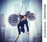 Small photo of Businessman hindered by balls balanced on rope