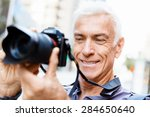 senior man with camera in city | Shutterstock . vector #284650640