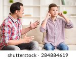 Small photo of Son closing ears while father scolding him.