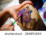 Girl Painting Stone With Purpl...