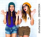 Small photo of Playful and carefree. Excited young girls dressed in stylish clothes casual wear shirts and shorts and colorful hats. The girls raised their hands, their long hair on a light background
